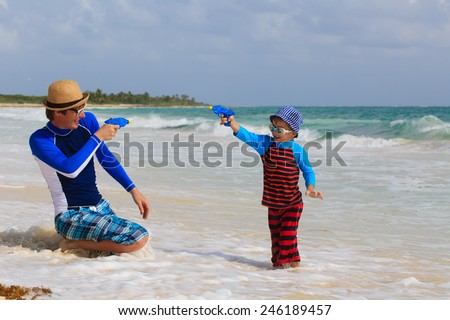 father and son playing with water guns on sea vacation