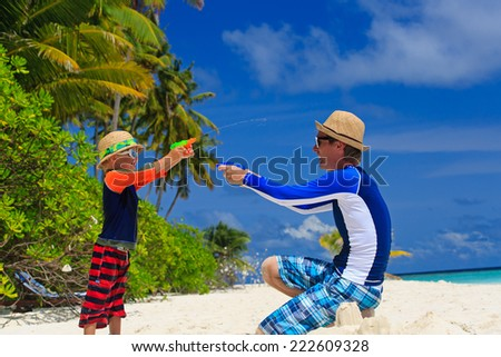 father and son playing with water guns on tropical beach