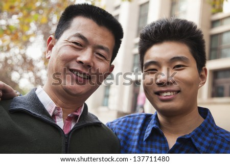 Father and son portrait in front of dormitory - stock photo