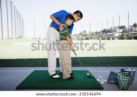 Father and Son Practicing Golf - stock photo