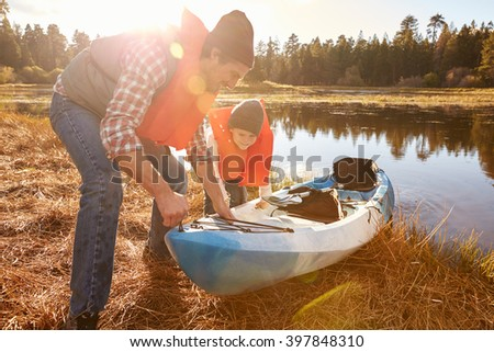 Father and son preparing kayak for launch from lakeside - stock photo