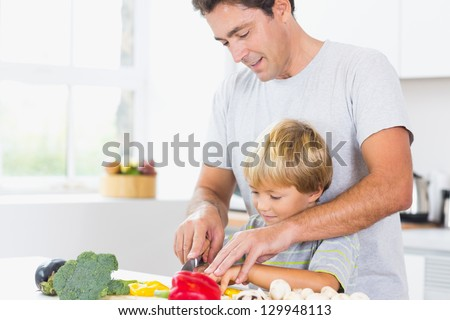 Father and son preparing vegetables together in kitchen