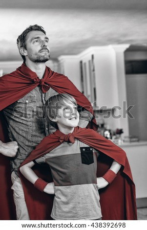 Father and son pretending to be superhero in living room at home - stock photo