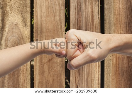 father and son punching fists/hands for agreement over a wooden background