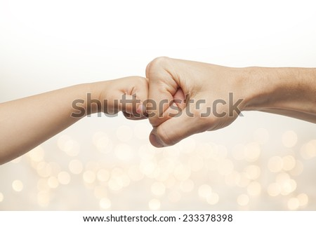father and son punching for agreement on christmas lights background  - stock photo