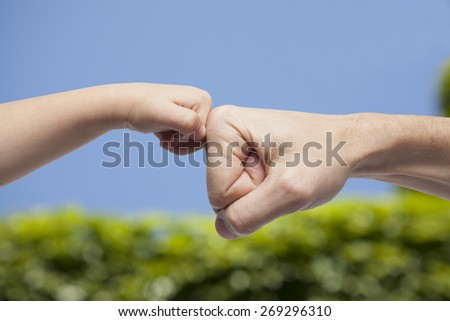 Father and son punching for agreement on nature background - stock photo