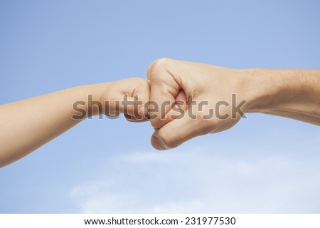 father and son punching for agreement on sky background - stock photo