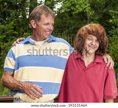 Father and son - punk-looking teenager with long dyed hair - laughing, having fun together