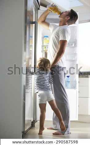Father And Son Raiding The Fridge For Drink - stock photo