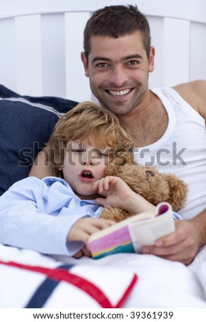 Father and son reading a book in bed together - stock photo