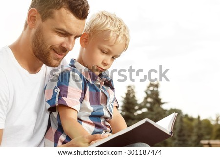 Father and son reading book in park - stock photo