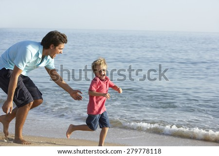 Father And Son Running Along Beach - stock photo