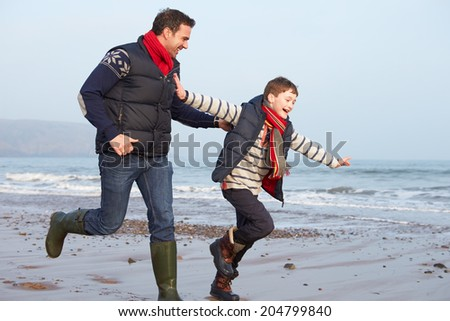 Father And Son Running On Winter Beach - stock photo