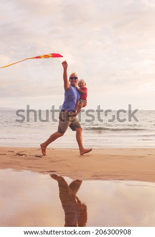 Father and son running with kite at the beach at sunset - stock photo