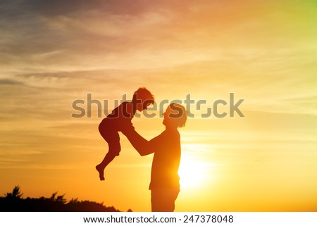 father and son silhouettes play at sunset - stock photo