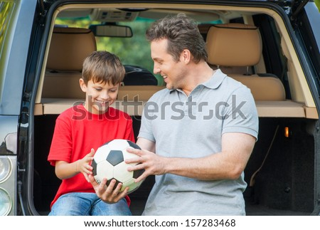 Father and son sit near car with opened boot and going to talk about football game - stock photo