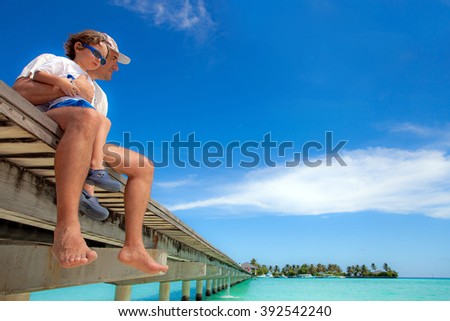 Father and son sit on a jetty, Maldive Island - stock photo