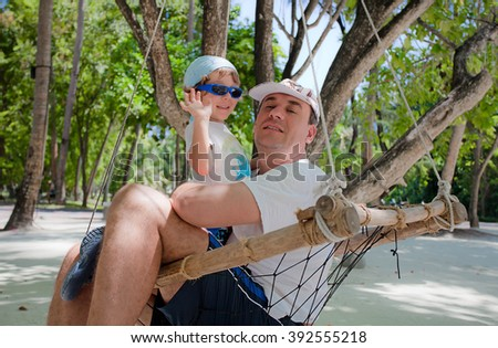 Father and son sits on an hammock in Maldive Island - stock photo