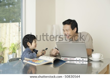 Father and son sitting at kitchen table together; laptop and coloring book on table - stock photo