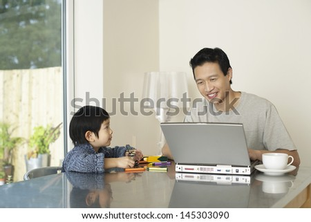 Father and son sitting at table with laptop and colors - stock photo