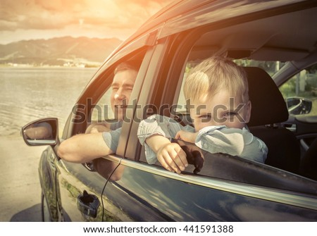 Father and son sitting in car