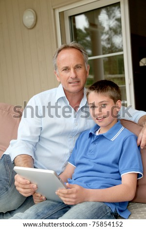 Father and son sitting in sofa with electronic tablet - stock photo
