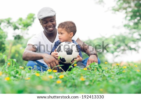 Father and son sitting in the park with a soccer ball - stock photo