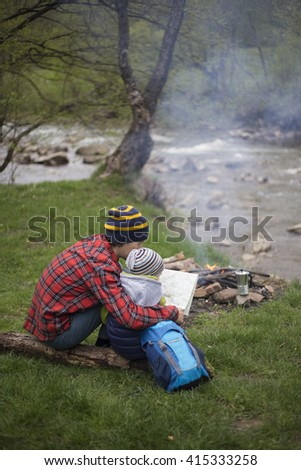Father and son sitting near a campfire at the campsite and are looking at the map. - stock photo