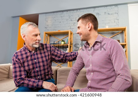 Father and son sitting on couch and having funny talk - stock photo