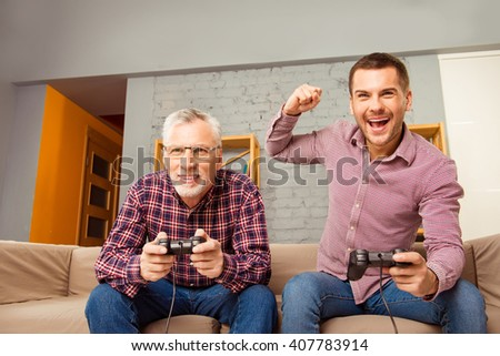 Father and son sitting on couch and playing video games - stock photo