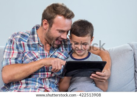 Father and son sitting on sofa and using digital tablet in living room - stock photo