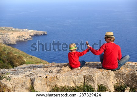 father and son sitting on top of a mountain, family travel - stock photo
