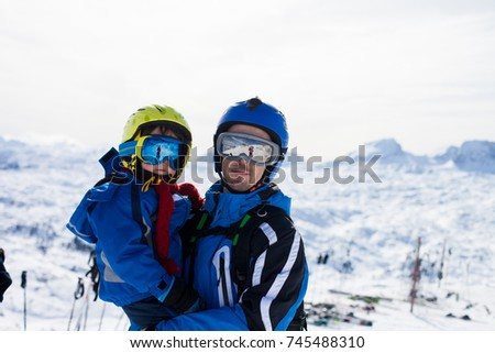 Father and son, skiing happily in Austrian ski resort in the mountains, wintertime