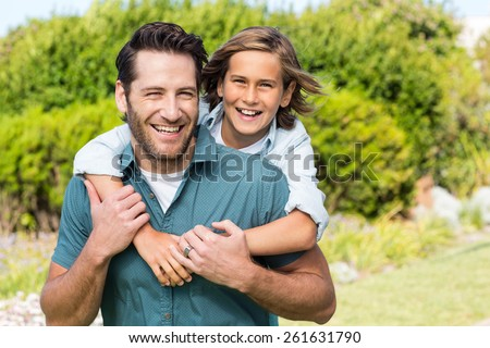 Father and son smiling at camera in the countryside - stock photo