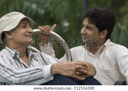 Father and son smiling in a park - stock photo