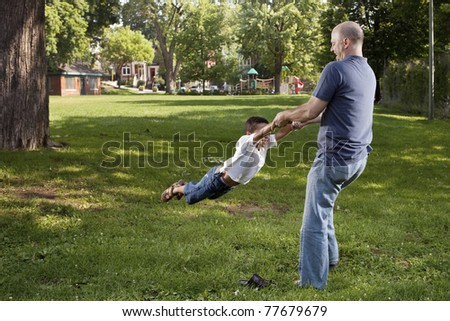 Father and son spinnig at the park - stock photo