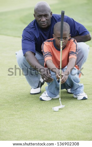 Father and son squatting on golf course - stock photo
