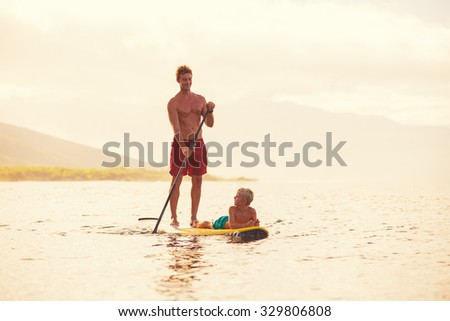 Father and son stand up paddling at sunrise, Summer fun outdoor lifestyle - stock photo