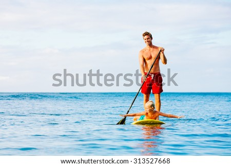 Father and Son Stand Up Paddling. Having Fun Outdoors. Summer Lifestyle. - stock photo