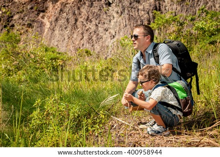 Father and son standing near the pond at the day time.  Concept of friendly family. - stock photo
