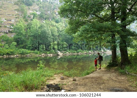 Father and son standing on the bank of the river - stock photo