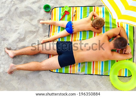 father and son sunbathing on colorful blanket - stock photo