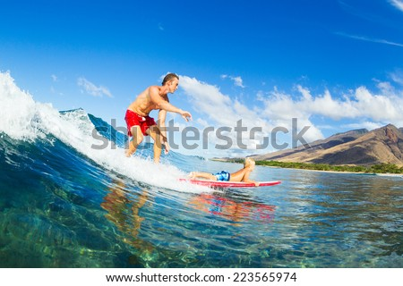 Father and Son Surfing Together. Riding Wave on Surfboard Tandem. Fatherhood, Family Fun Outdoor Lifestyle. - stock photo