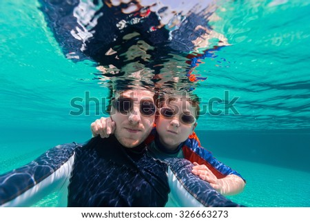 Father and son swimming underwater and making selfie