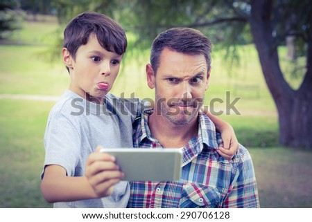 Father and son taking a selfie in the park on a sunny day - stock photo