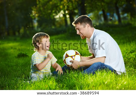 Father and son talk, sitting in park with a football - stock photo
