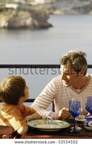 father and son talking at restaurant - stock photo