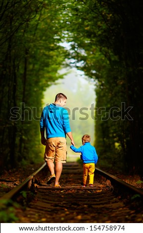 father and son together in railway green tunnel - stock photo
