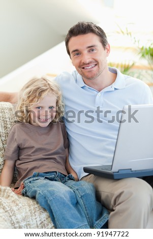 Father and son together on sofa with laptop