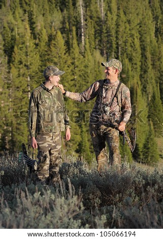 father and son together outdoors with archery hunting gear and camouflage clothing - stock photo